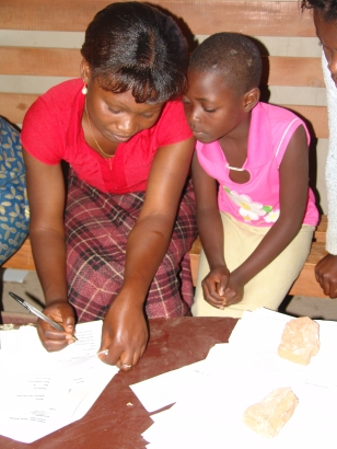 Teacher filling out a salvation response card with a child, Zambia 2004